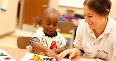 A pediatric patient enjoys painting in the child life center