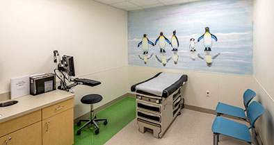 An exam room's wall has a bright, kid-friendly wall mural of penguins.