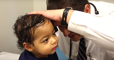 Palm Bay pediatrician, Julio Pajaro, MD, examines the ear of a young patient.