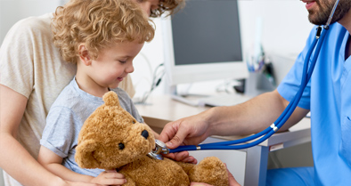 Nemours physicians helping a child — and teddy — with an aerodigestive disorder.