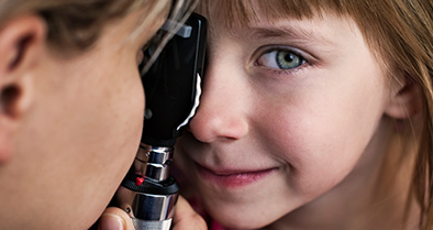 Young girl being examined for amblyopia (lazy eye) by a Nemours eye specialist.