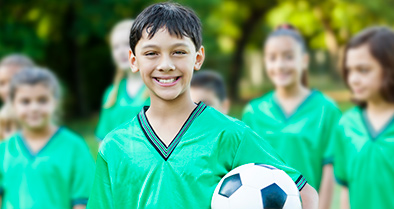 Smiling boy playing soccer, years after treatment at nemours for Anomalous Coronary Artery.
