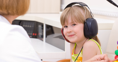 Smiling girl taking a hearing test for Central Auditory Processing Disorder (CAPD).