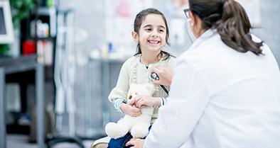 Nemours cardiologist examines smiling little girl for possible cardiomyopathy.