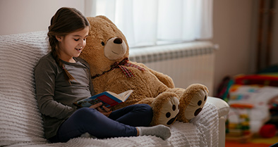 Little girl recovered from heart failure reading next to a big stuffed bear.