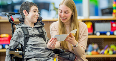 Therapist reading a booklet to a young boy with a neuromuscular disorder, in a wheelchair.