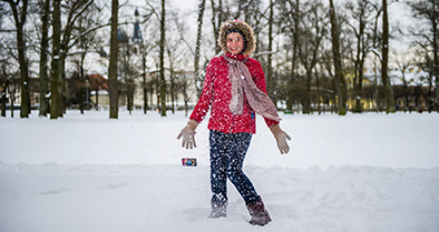 Girl in coat playing in snow after treatment at Nemours for pulmonary embolism.