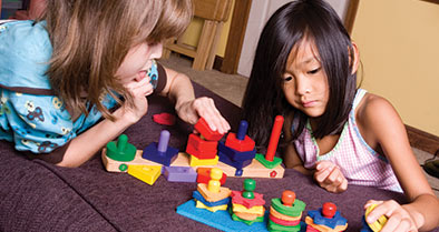 Two girls focus on an activity at the Swank Autism Center.