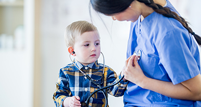 Nemours doctor checking boy for transposition of the great arteries lets him check her with her stethoscope.