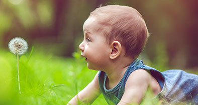 Young child with truncus arteriosus outside, crawling in grass.