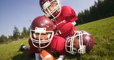 Boys playing football while wearing helmets to help prevent concussions in children.