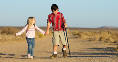 Boy with Limb Length Discrepancy walking with one crutch, his younger sister beside him.