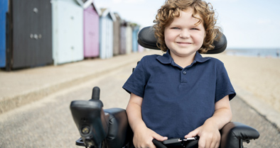 Child with muscular dystrophy in a wheelchair at the beach, smiling.