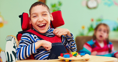 Smiling boy with spinal muscular atrophy in a wheelchair.