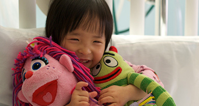 Smiling girl pediatric cardiology patient lies in bed and holds stuffed animals