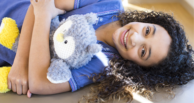 Teen girl pediatric dermatology patient lies down, hugging teddy bear.