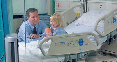 One of Nemours pediatric hospitalists talks to a patient at her bedside.