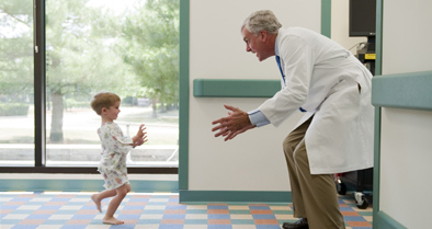 Boy running to pediatric orthopedic surgeon with arms open.