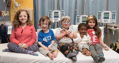 Five Nemours patients with osteogenesis imperfecta (OI) sit on a hospital bed.