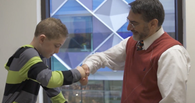 Young boy shakes hands with Nemours plastic surgeon.