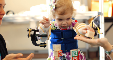 Pediatric physical medicine expert working with girl wearing arm device and playing with blocks.