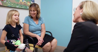 Pediatric rheumatology doctor talks to girl and her mom