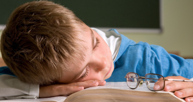 Young boy with sleep issue sleeping at school.