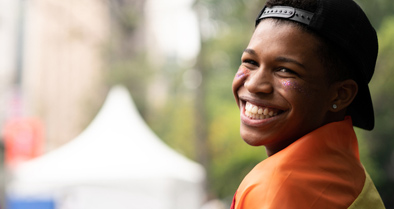 A teen smiling about the help our Gender Wellness Program offers.