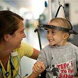 Pediatric orthopedic boy patient wearing a halo smiles at AI nurse