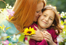 Patient satisfaction: Happy mother and daughter in field of flowers.