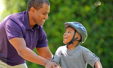 kid in a helmet gets help learning to ride a bike
