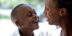 Smiling boy with pediatric orthopedic problem looks up at smiling mom