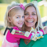 Mom holds girl arthrogryposis patient with robotic arm device at AI