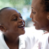 Smiling boy with neuromuscular disorder looks up at smiling mom at AI