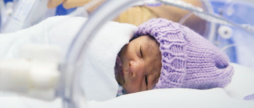 A tiny newborn in an incubator diagnosed with perinatal conditions